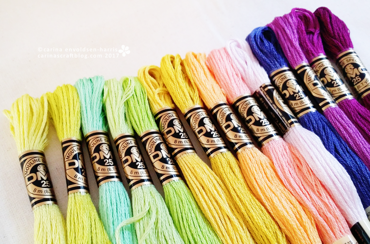 Skeins of embroidery thread in yellow, green and purple.