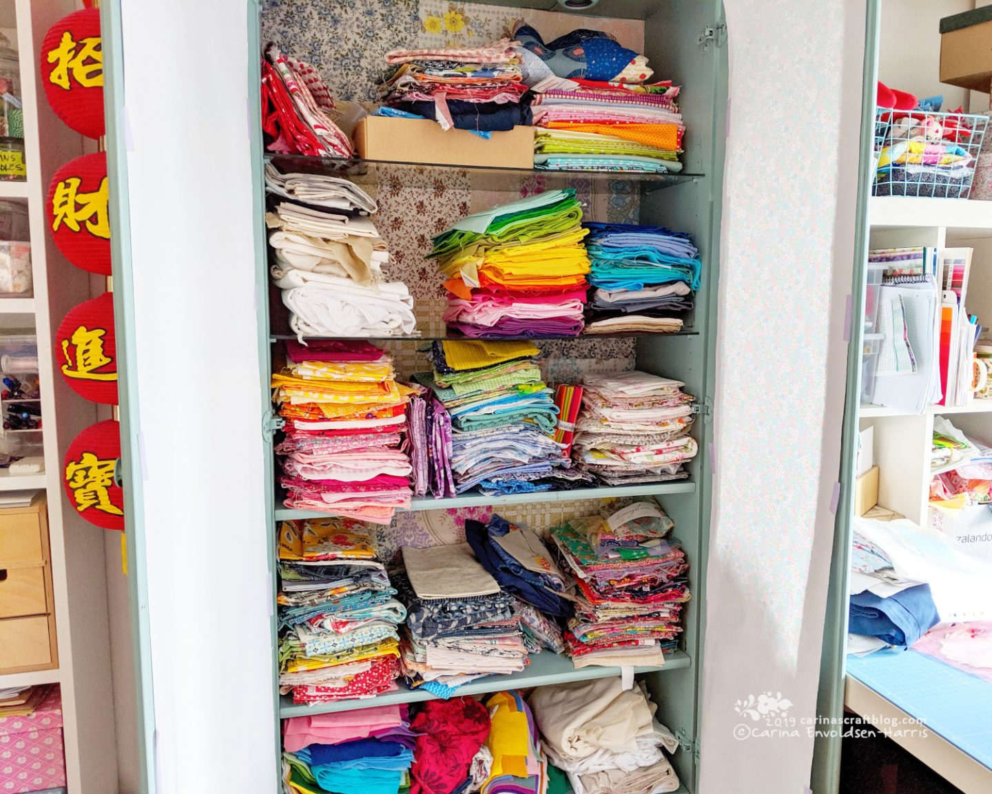 A tall cabinet with glass shelves, doors open so tidy stacks of fabric can be seen.