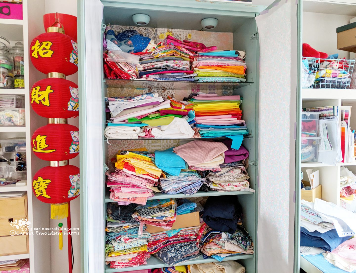 A tall cabinet with glass shelves, doors open so messy stacks of fabric can be seen.