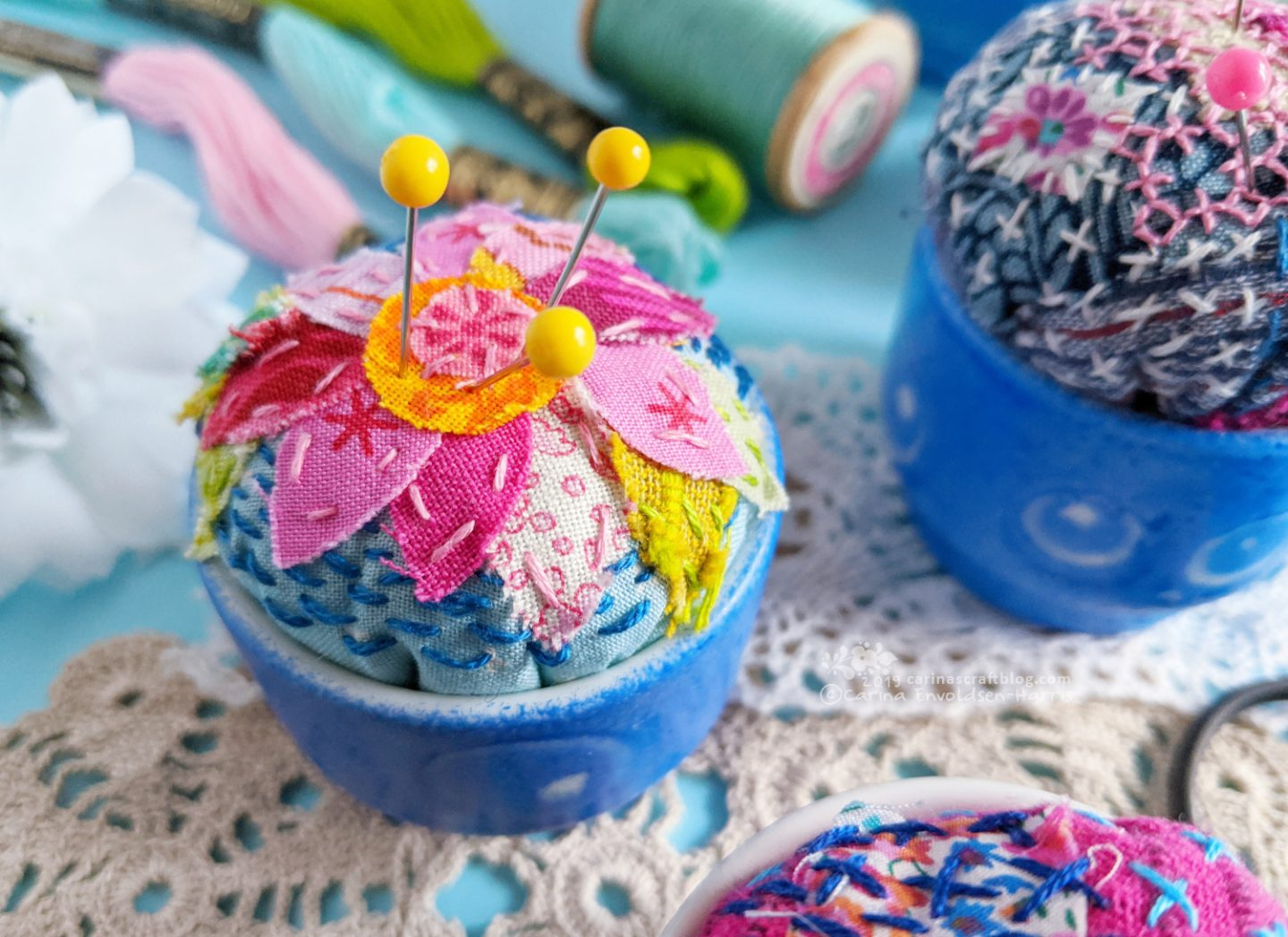 Egg cups turned into pincushions. Decorated with fabric scraps and stitching.