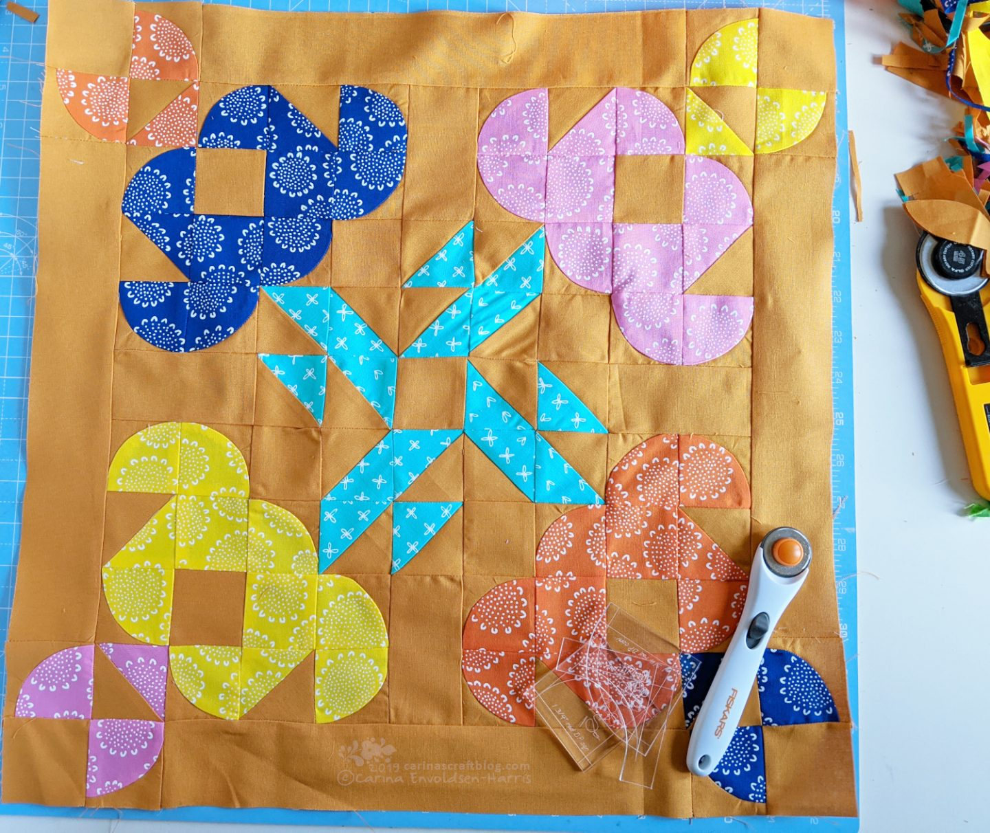Mini quilt top with four stylized tulips.