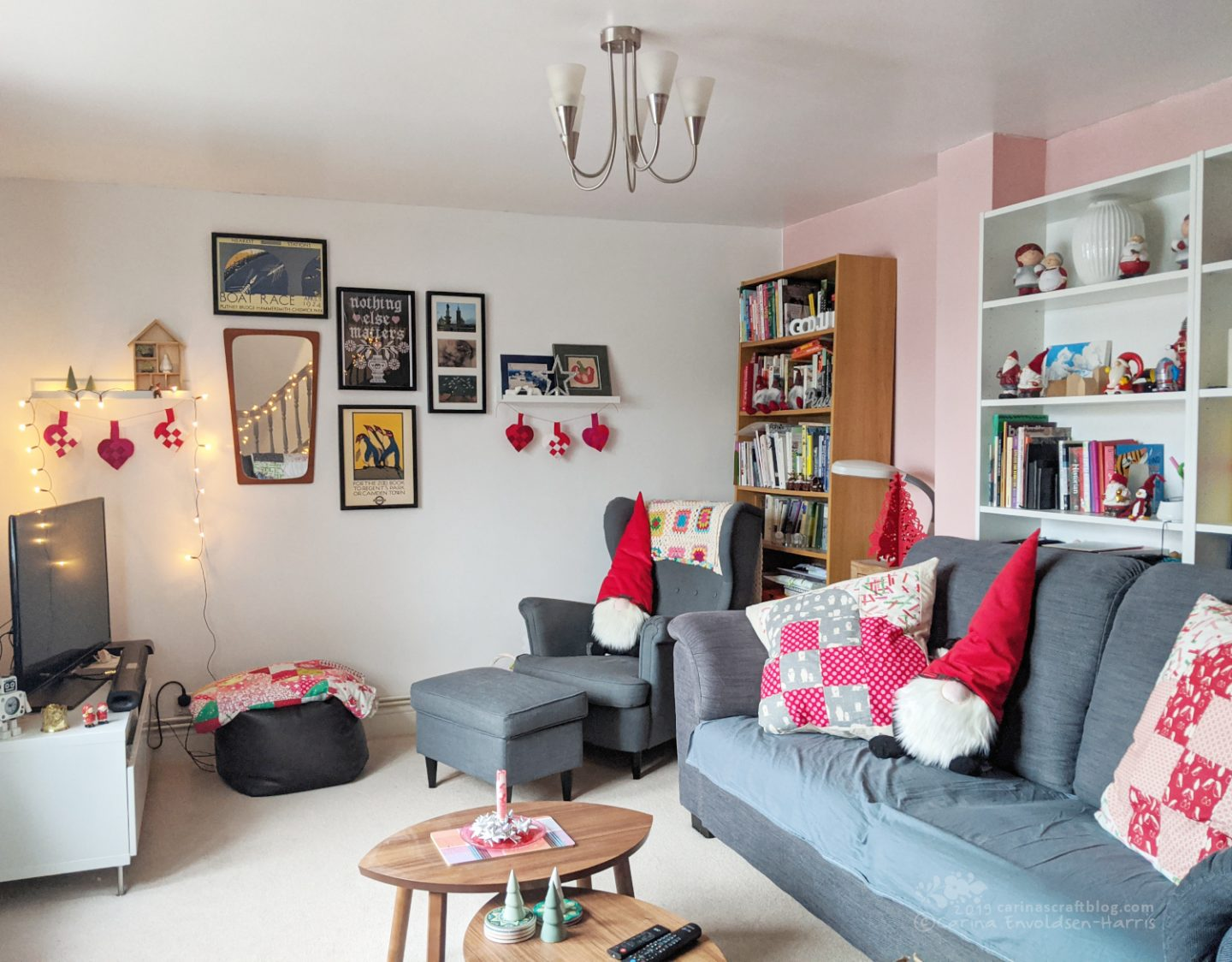 Living room with grey sofa and arm chair. Decorated with Christmasy cushions and other decorations, mainly in red and white.
