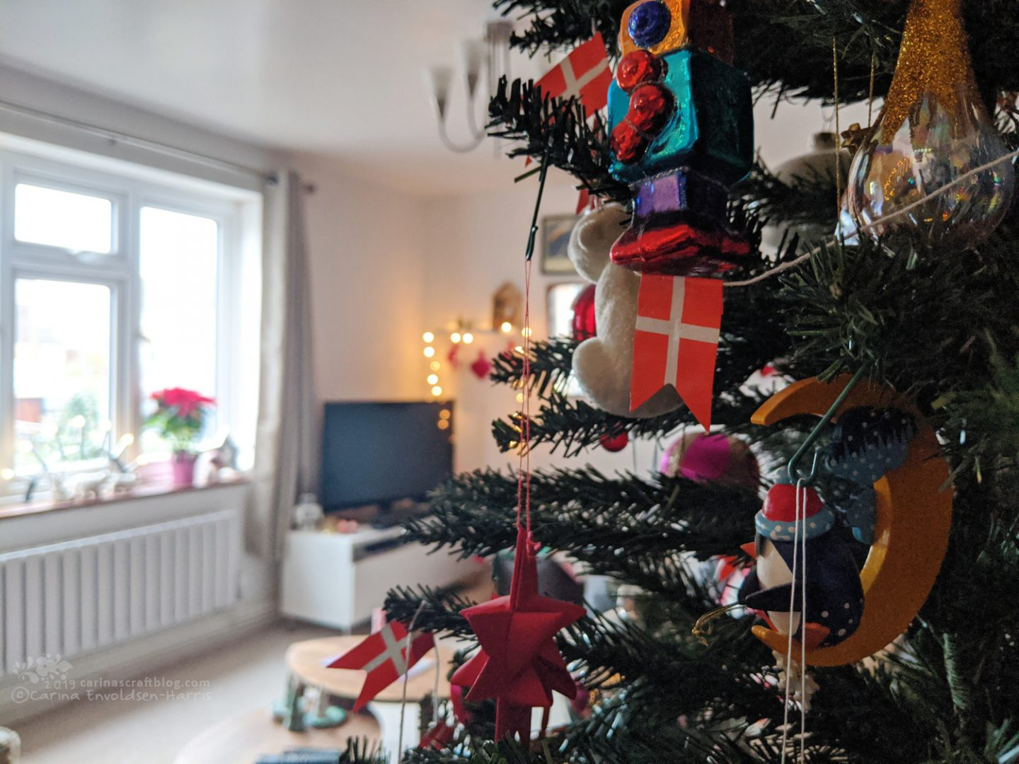 Decorated Christmas tree in half of the picture, in the background a tv and a window,