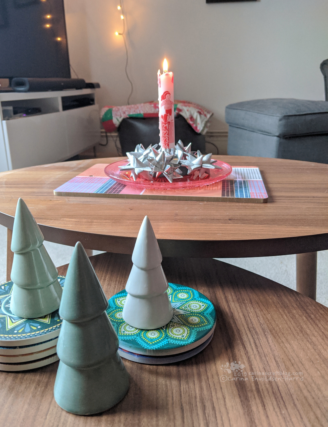 Coffee table with ceramic Christmas trees and an advent candle.