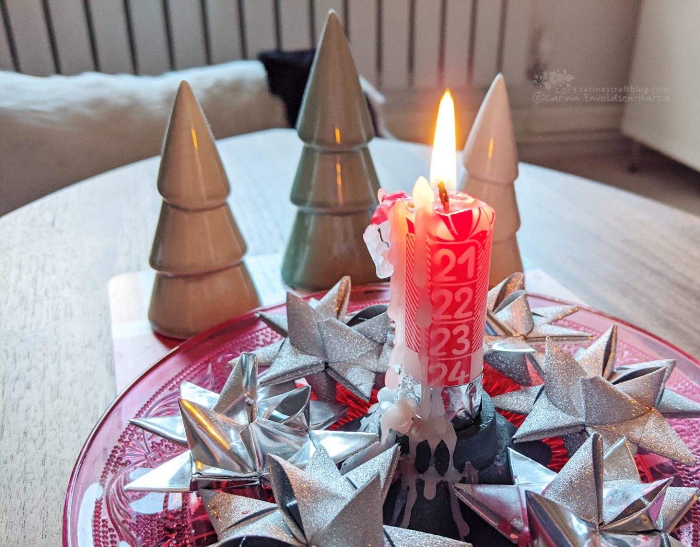 Almost burnt down advent candle surrounded by silver woven paper stars.