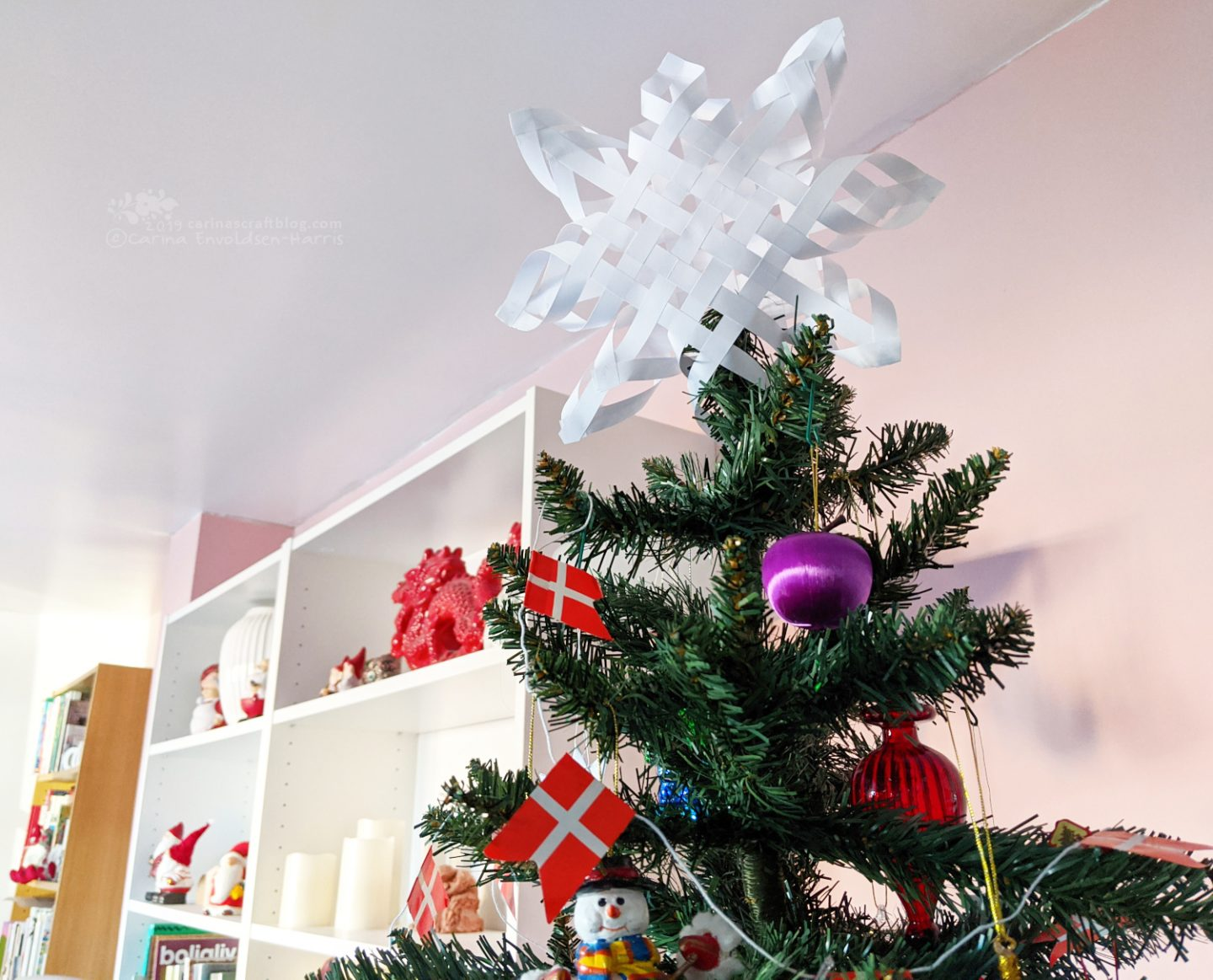 Decorated Christmas tree with woven paper star topper.