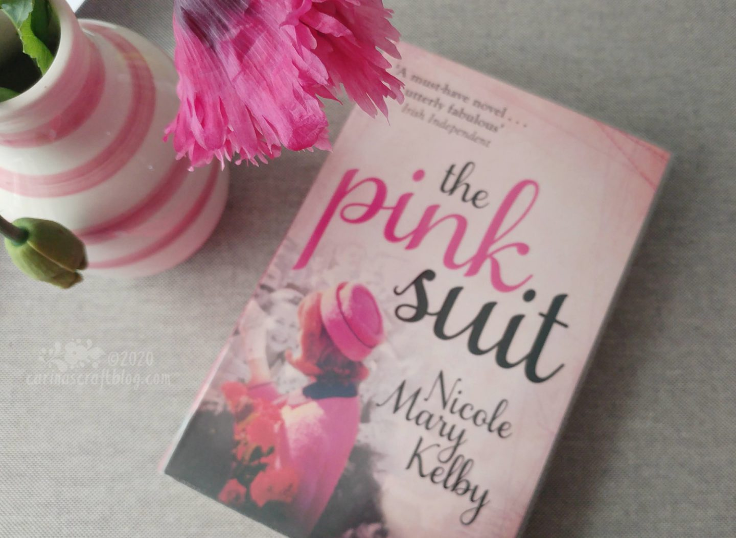 Book The Pink Suit next to a vase with a pink poppy.