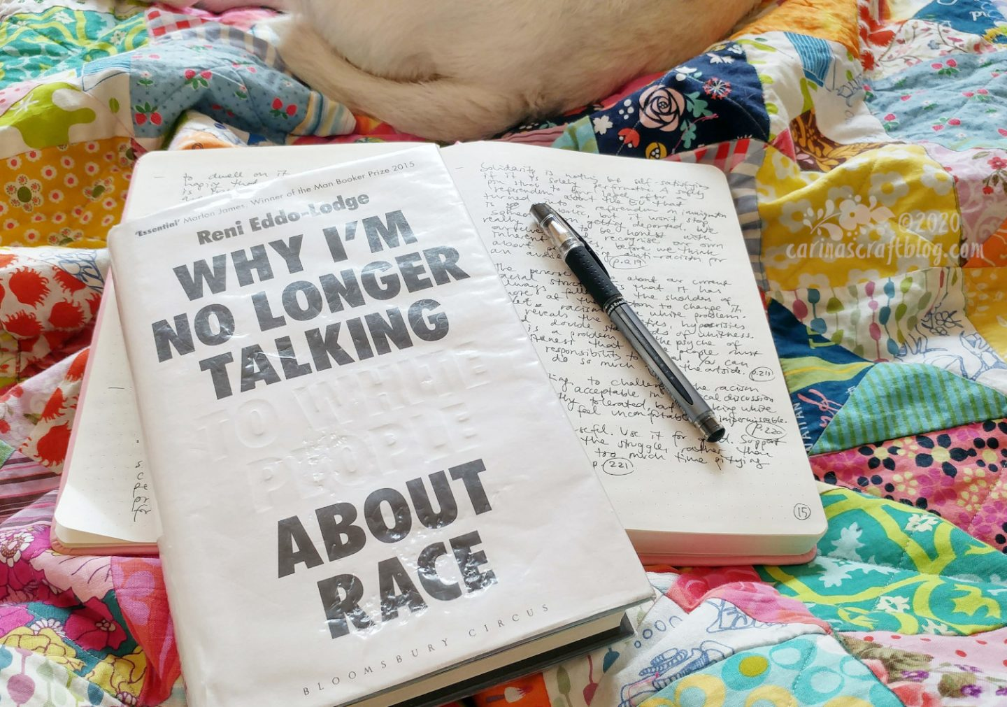Book Why I'm No Longer Talking to White People About Race on top of open notebook