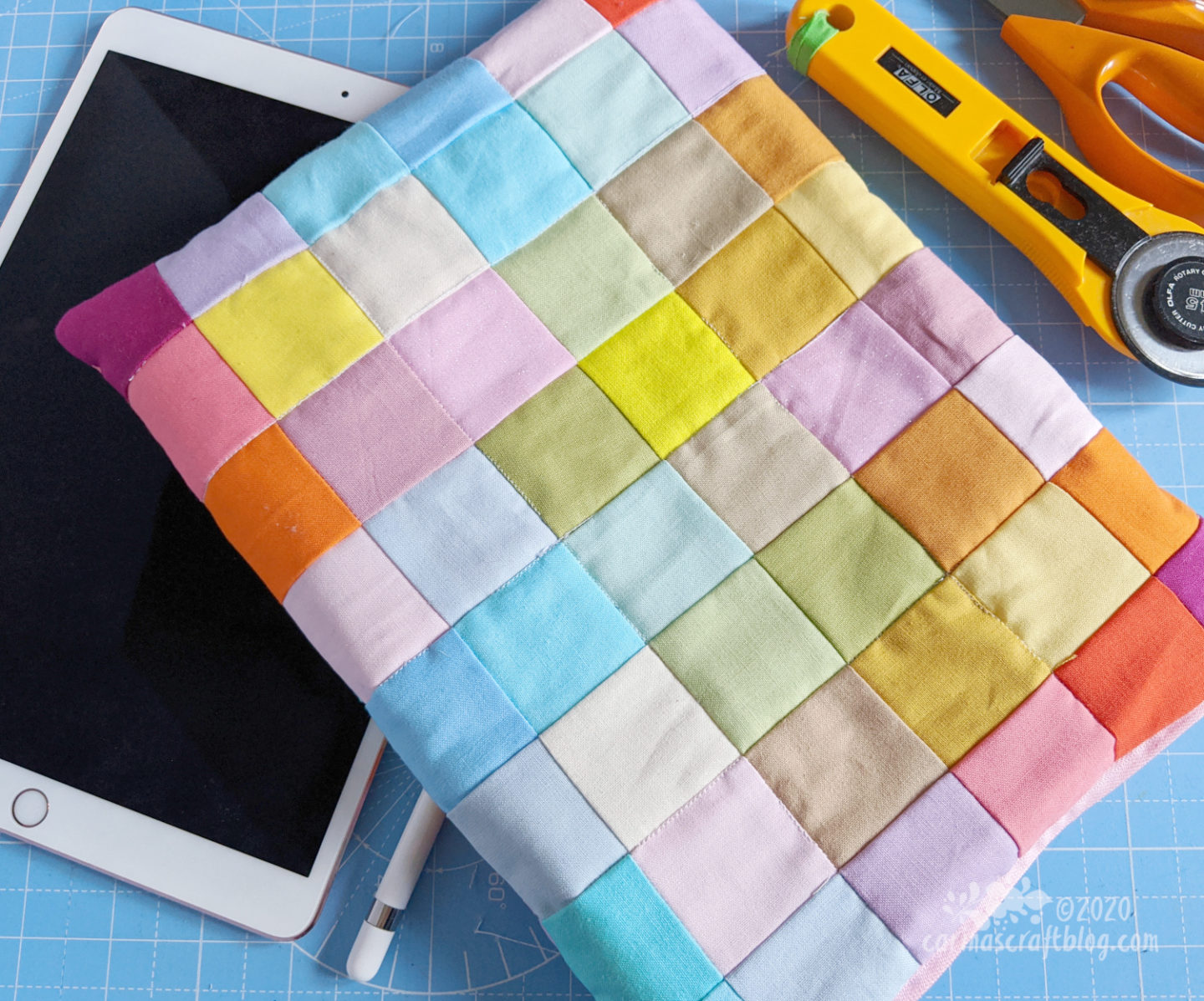 Patchwork cover with squares in pastel colours placed on an ipad.